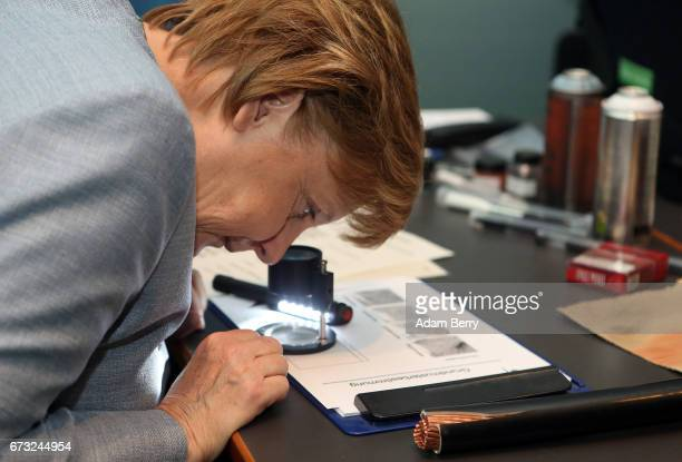 German Chancellor Angela Merkel tries out a lupe to look at fingerprints at the Bundespolizei stand at Girls' Day on April 26 2017 in Berlin Germany...