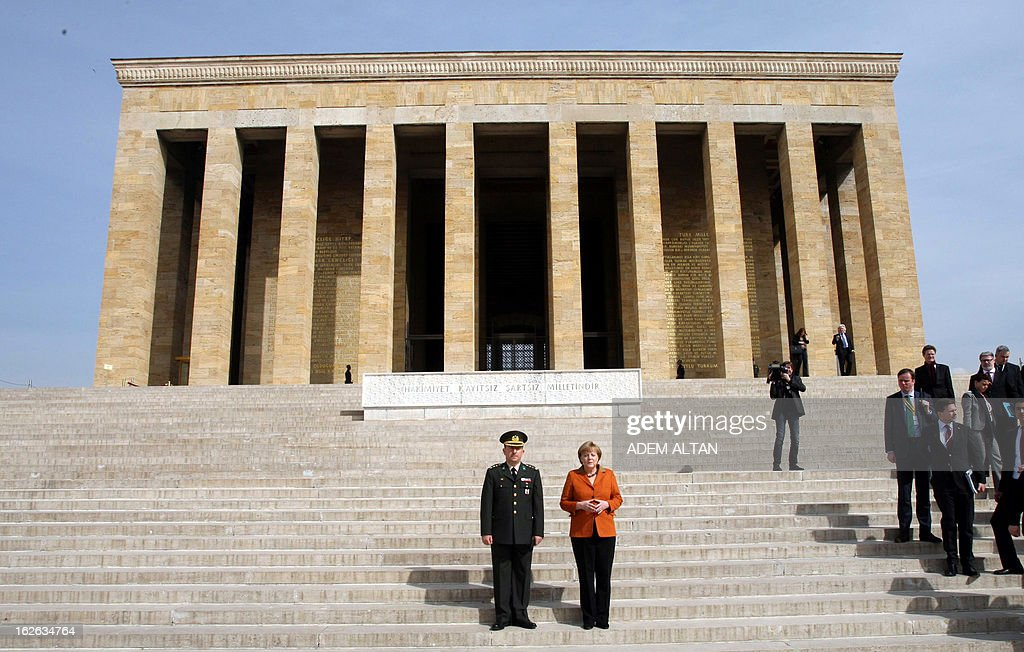 German Chancellor Angela Merkel (C, R) Turkish army col. Muzaffer Taytak pose in front of the mausoleum of Turkey's Republic's founder Kemal Ataturk in Ankara, on February 25, 2013, on the second an final day of her official visit to Turkey. AFP PHOTO ADEM ALTAN