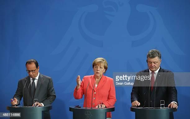 German Chancellor Angela Merkel Ukrainian President Petro Poroshenko and French President Francois Hollande speak to the media following talks at the...