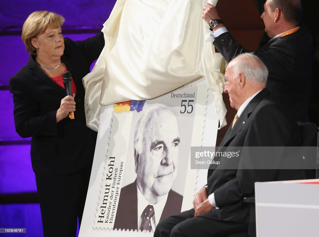 German Chancellor <a gi-track='captionPersonalityLinkClicked' href=/galleries/search?phrase=Angela+Merkel&family=editorial&specificpeople=202161 ng-click='$event.stopPropagation()'>Angela Merkel</a> (L) unveils a commemorative postal stamp showing former German Chancellor <a gi-track='captionPersonalityLinkClicked' href=/galleries/search?phrase=Helmut+Kohl&family=editorial&specificpeople=202518 ng-click='$event.stopPropagation()'>Helmut Kohl</a> as Kohl (R) looks on at a gala evening in Kohl's honour at the Deutsches Museum on September 27, 2012 in Berlin, Germany. Guests from politics, church and society attended the event to honour Kohl on the 30th anniversary of Kohl becoming chancellor. During his chancellorship Kohl facillitated the end of the Cold War, the fall of the Berlin Wall and German reunification.