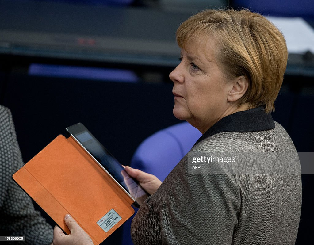 German chancellor Angela Merkel uses an iPad at the lower house of parliament, Bundestag, on December 13, 2012 in Berlin on the position Germany will take at an EU summit due to begin later in the day. Merkel praised on Thursday a European Union agreement to create a bank supervisor to oversee lenders across the eurozone.