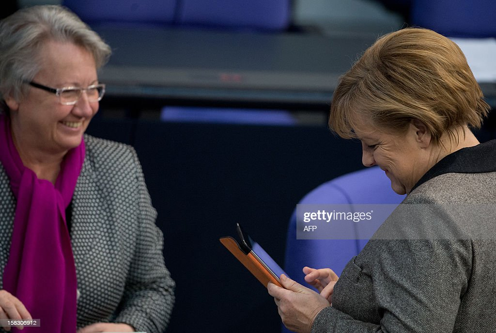 German chancellor Angela Merkel (R) uses an iPad at the lower house of parliament, Bundestag, on December 13, 2012 in Berlin on the position Germany will take at an EU summit due to begin later in the day. Merkel praised on Thursday a European Union agreement to create a bank supervisor to oversee lenders across the eurozone. AFP PHOTO / JOHANNES EISELE