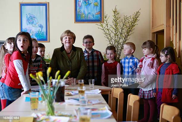 German Chancellor Angela Merkel visits a child day care center on March 13 2013 in Neumuenster Germany According to recent studies Germany is short...