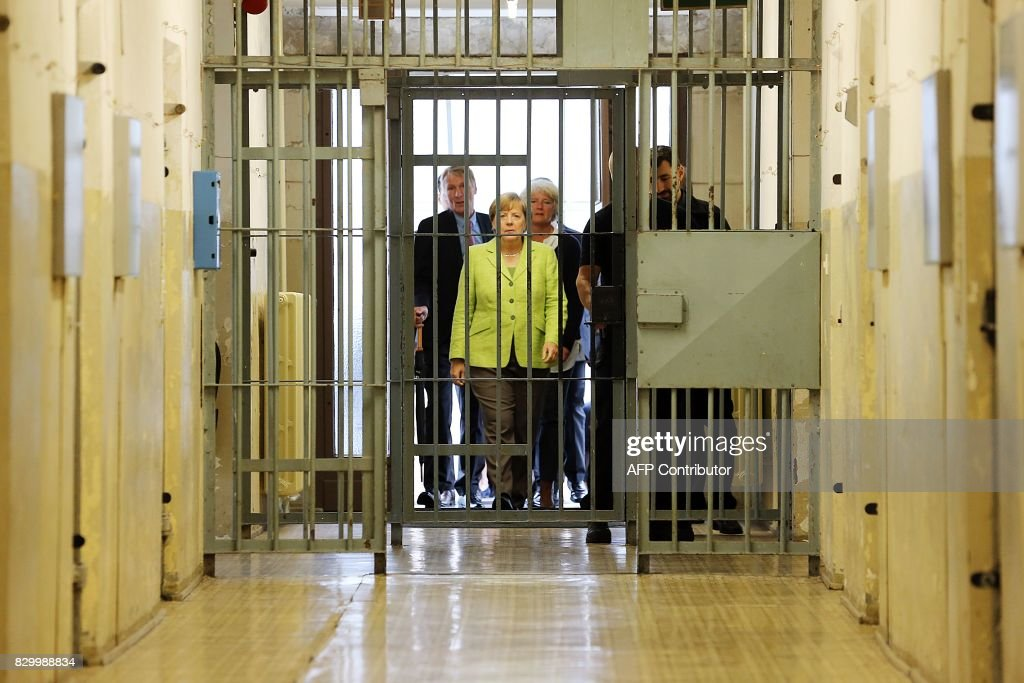TOPSHOT - German Chancellor Angela Merkel (C) visits the Berlin-Hohenschönhausen Memorial at the site of a former prison of the East German Ministry of State Security (MfS; 'Stasi') in Berlin on August 11, 2017. Thousands of political prisoners passed through this jail, including nearly all the prominent figures who opposed the regime of the German Democratic Republic (GDR). / AFP PHOTO / POOL / Wolfgang Kumm