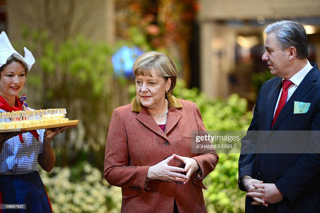 German Chancellor Angela Merkel (C) visits the Netherlands booth with Berlin Mayor Klaus Wowereit (R) as she opens the Gruene Woche Agricultural Fair in Berlin on January 18, 2013. This year the official partner country of the fair is The Netherlands. EISELE