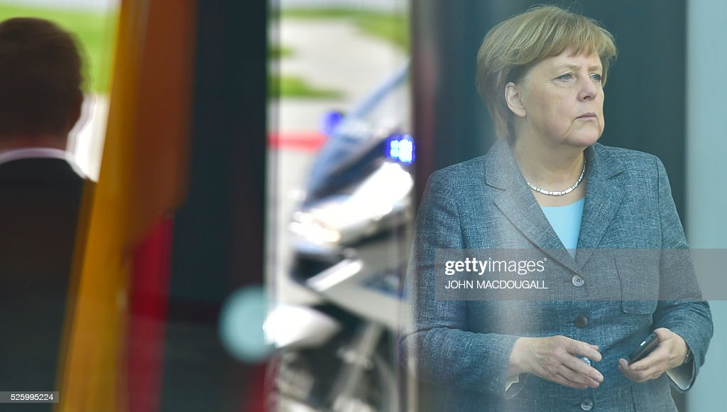 German Chancellor Angela Merkel waits for her guest the Latvian Prime Minister on April 29, 2016 at the Chancellery in Berlin. / AFP / John MACDOUGALL
