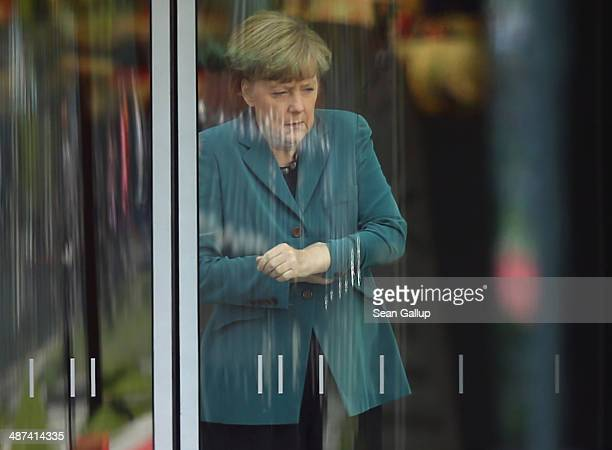 German Chancellor Angela Merkel waits for the arrival of Japanese Prime Minister Shinzo Abe inside a glass door of the Chancellery on April 30 2014...