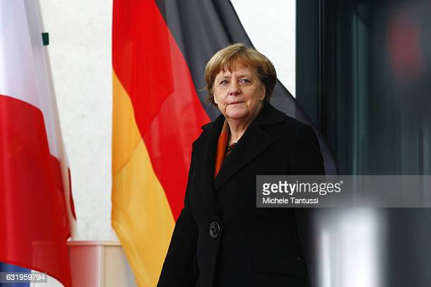German Chancellor Angela Merkel waits for the Italian Prime Minister Paolo Gentiloni before they review a guard of honor upon Gentilon's arrival at...