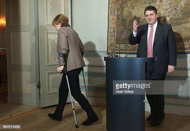 German Chancellor Angela Merkel walking with crutches due to an injured while skiing and Vice Chancellor and Economy and Energy Minister Sigmar...