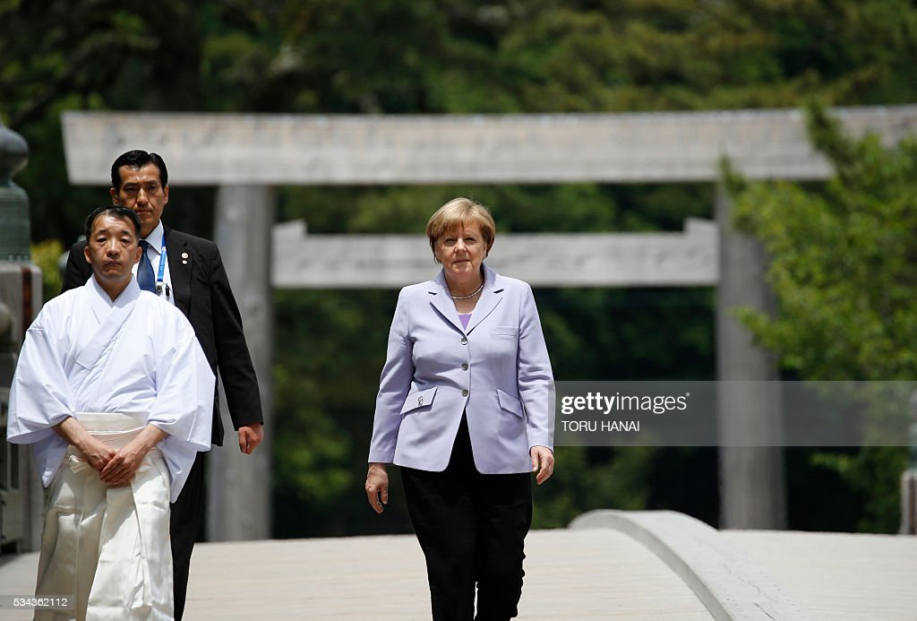 German Chancellor Angela Merkel (R) walks across Ujibashi bridge as she visits Ise-Jingu Shrine in the city of Ise in Mie prefecture, on May 26, 2016, on the first day of the G7 leaders summit. World leaders kick off two days of G7 talks in Japan on May 26 with the creaky global economy, terrorism, refugees, China's controversial maritime claims, and a possible Brexit headlining their packed agenda. / AFP / POOL / TORU