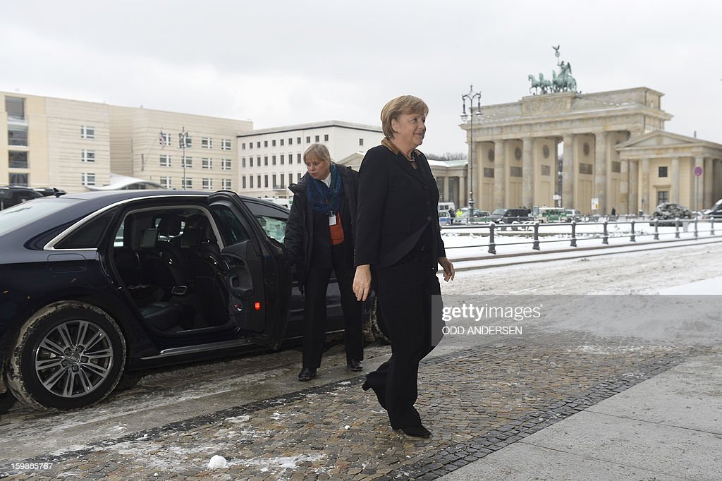 German Chancellor Angela Merkel (C) walks in front of the Brandenburg Gate as she arrives to meet with French President at the French Embassy in Berlin on January 22, 2013 for a meeting as part of the celebration to mark 50 years since the Elysee Treaty launched after WWII the French-German cooperation. Merkel is to meet there with Francois Hollande. In signing the landmark treaty on January 22, 1963, then French president Charles de Gaulle and West German chancellor Konrad Adenauer sealed a new era of reconciliation between the former foes which has since driven European unity. AFP PHOTO / ODD ANDERSEN