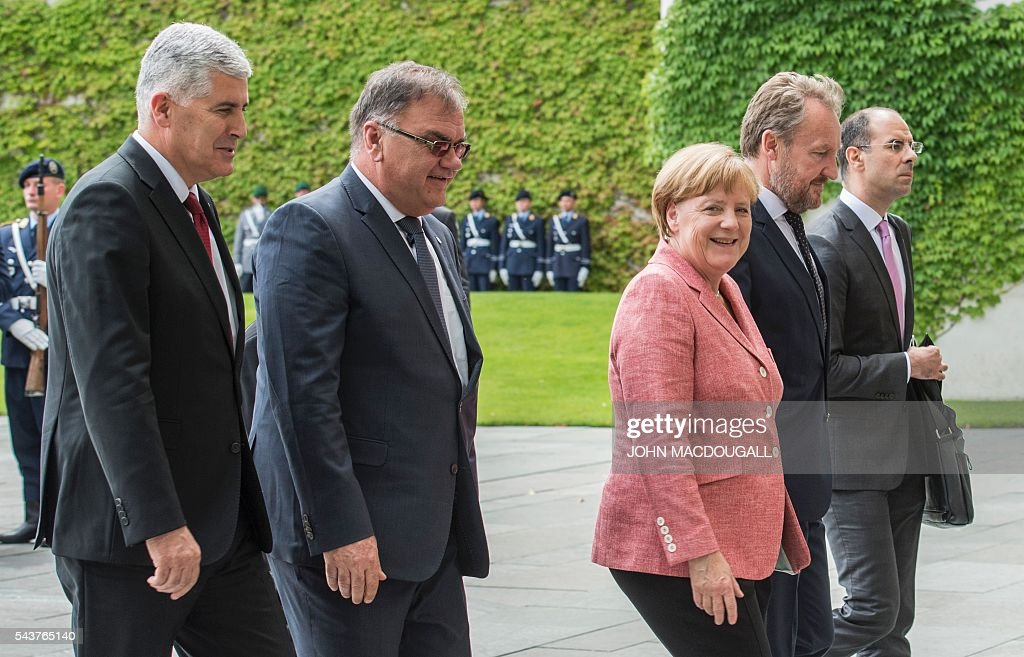 German Chancellor Angela Merkel (2nd from R) walks into the chancellery building with the three members of the Presidency of Bosnia and Herzegovina Dragan Covic (L), Bakir Izetbegovic (2nd from R) and Mladen Ivanic (2nd from L) during a welcoming ceremony at the chancellery in Berlin on June 30, 2016. / AFP / JOHN