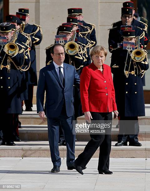 German Chancellor Angela Merkel walks next to French President Francois Hollande during a welcoming ceremony prior to the 18th FrancoGerman cabinet...