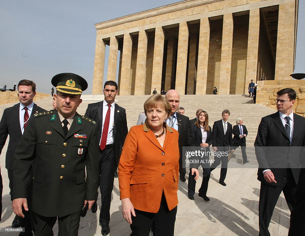 German Chancellor Angela Merkel (C) walks next to Turkish army Col. Muzaffer Taytak (L) as she visits the mausoleum of Turkey's Republic's founder Kemal Ataturk in Ankara, on February 25, 2013, on the second an final day of her official visit to Turkey.