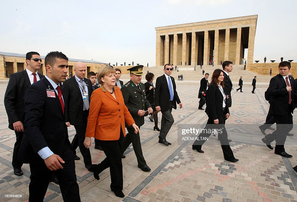 German Chancellor Angela Merkel (5thL) walks next to Turkish army Col. Muzaffer Taytak (C) as she visits the mausoleum of Turkey's Republic's founder Kemal Ataturk in Ankara, on February 25, 2013, on the second an final day of her official visit to Turkey.