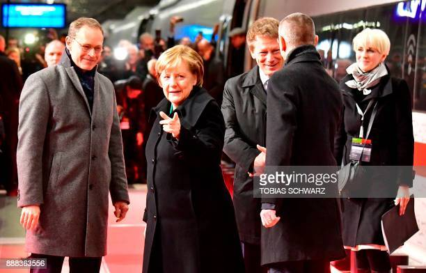 German Chancellor Angela Merkel walks on a platform next to mBerlin's mayor Michael Mueller and Chairman of German railway operator Deutsche Bahn...