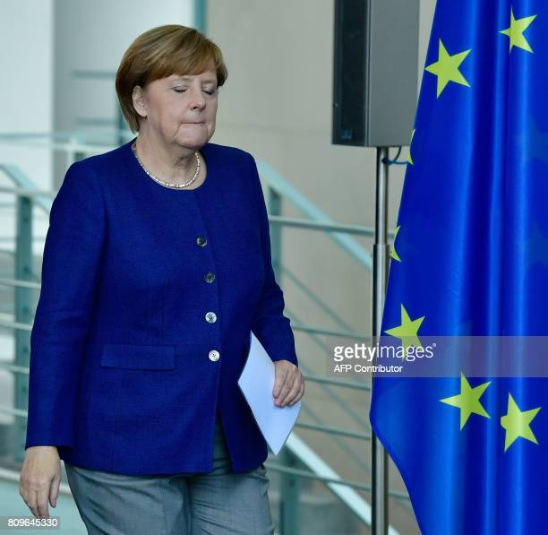 German Chancellor Angela Merkel walks past a flag of the European Union as she arrives to give a joint press conference with the Prime Minister of...
