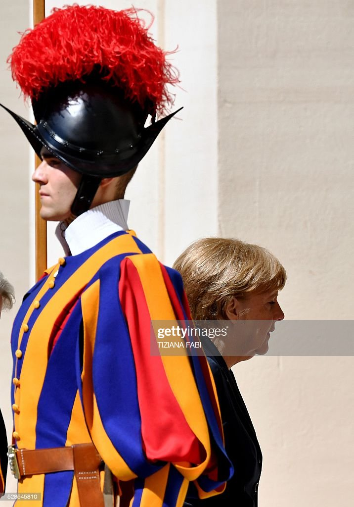 German Chancellor Angela Merkel walks past a Swiss guard as she arrives at the Vatican on May 6, 2016 for an audience with Pope Francis. Merkel is in Rome to take part in a ceremony for the awarding of Germany's famed Charlemagne Prize to Pope Francis, given to public figures in recognition of contribution to European unity. / AFP / TIZIANA