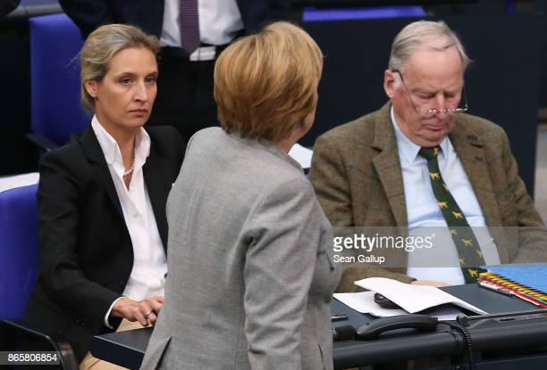 German Chancellor Angela Merkel walks past Alexander Gauland and Alice Weidel of the rightwing Alternative for Germany during the opening session of...