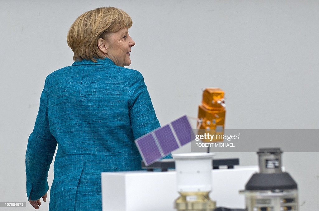 German Chancellor Angela Merkel walks past Autonomous Star Sensors, that are flight proven sensor autonomous star tracking systems for long-term GEO and LEO missions for telecommunication, science and Earth observation satellites during a visit at the Jena-Optronik GmbH (Ltd) on May 2 , 2013 in Jena, eastern Germany. AFP PHOTO / ROBERT MICHAEL