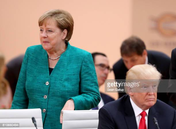 German Chancellor Angela Merkel walks past US President Donald Trump prior to the morning working session on the second day of the G20 economic...