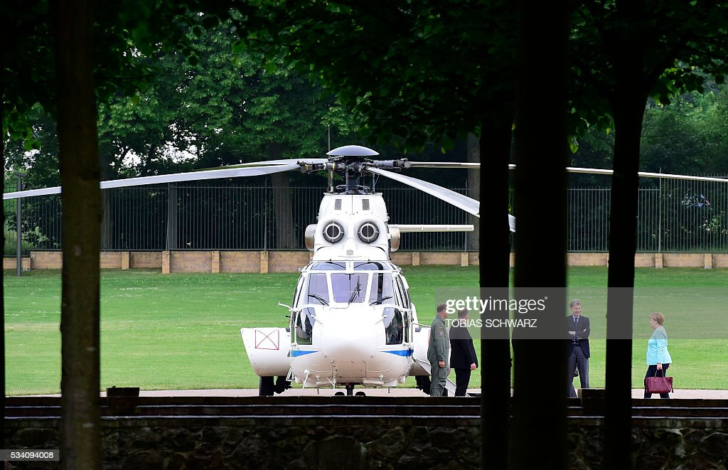 German Chancellor Angela Merkel walks to a helicopter after a news conference on a meeting of the German government at the Meseberg castle guest house on May 25, 2016. / AFP / TOBIAS