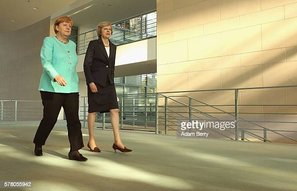 German Chancellor Angela Merkel walks with new British Prime Minister Theresa May as they arrive for a press conference on July 20 2016 in Berlin...