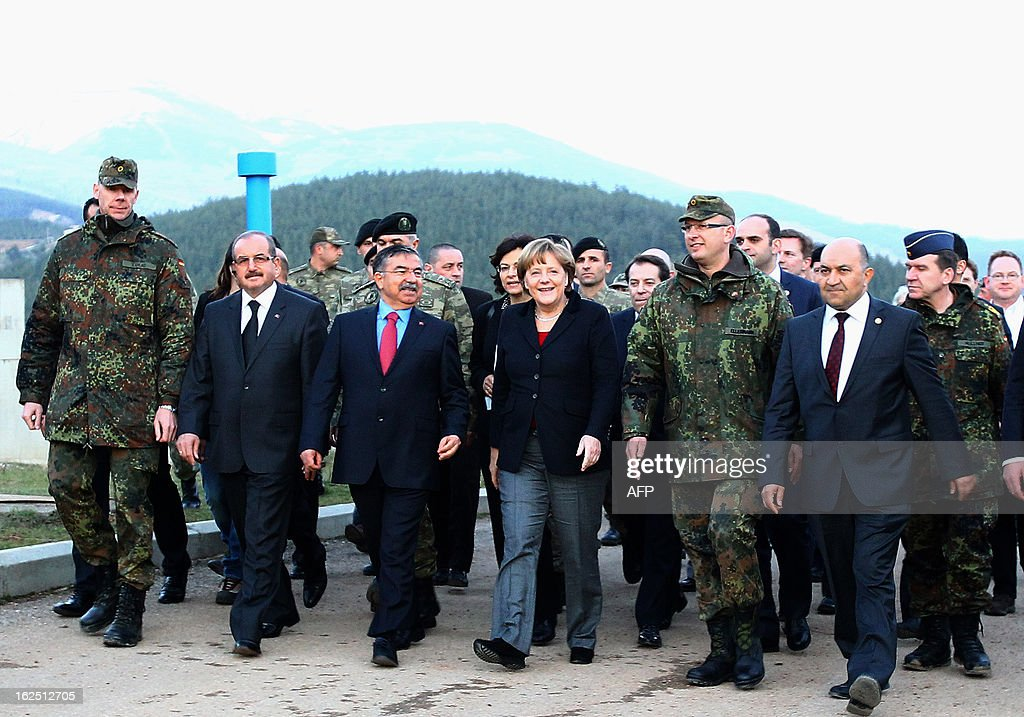 German Chancellor Angela Merkel (C) walks with Turkish Defence Minister Ismet Yilmaz (3th-L) as she visits the site where Patriot missile batteries are installed near the city of Kahramanmaras, February 24, 2013. Germany's defence minister inspected Patriot missile batteries close to the Syria-Turkey border on Saturday and said they delivered a 'clear warning' to Damascus that NATO would not tolerate missiles being fired into Turkey. AFP PHOTO/STR