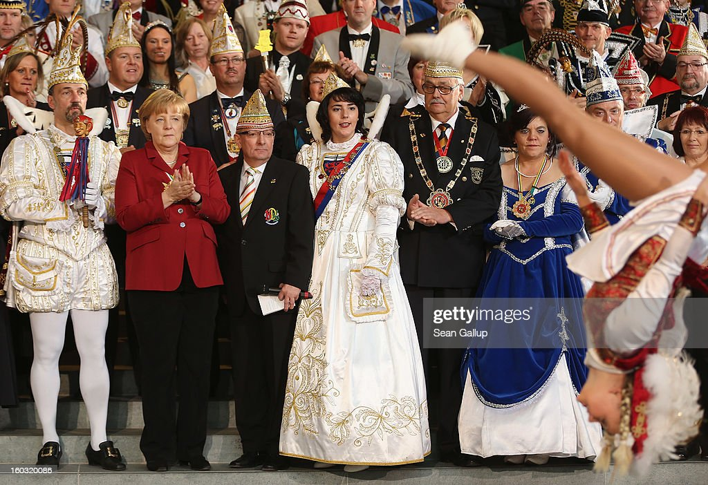 German Chancellor <a gi-track='captionPersonalityLinkClicked' href=/galleries/search?phrase=Angela+Merkel&family=editorial&specificpeople=202161 ng-click='$event.stopPropagation()'>Angela Merkel</a> (L) watches a Carnival dancer perform as Carnival delegates from all over Germany look on on January 29, 2013 in Berlin, Germany. Merkel received the delegates at an annual ceremony at the Chancellery. Germany is in the midst of Carnival season, which ends with its highpoint between Rose Monday and Ash Wednesday in a tradition common in several countries in Europe and the Americas.