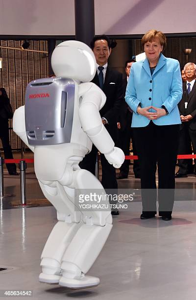 German Chancellor Angela Merkel watches a jumping performance by Japanese auto giant Honda Motor's humanoid robot Asimo as museum head and former...