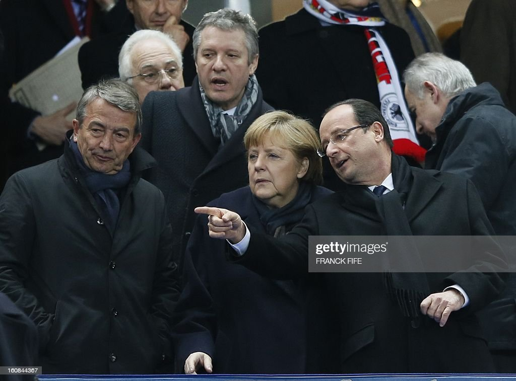 German Chancellor Angela Merkel (C) watches as French President Francois Hollande points during a friendly international football match between France and Germany on February 6, 2013 at the Stade de France in Saint-Denis, near Paris. AFP PHOTO / FRANCK FIFE