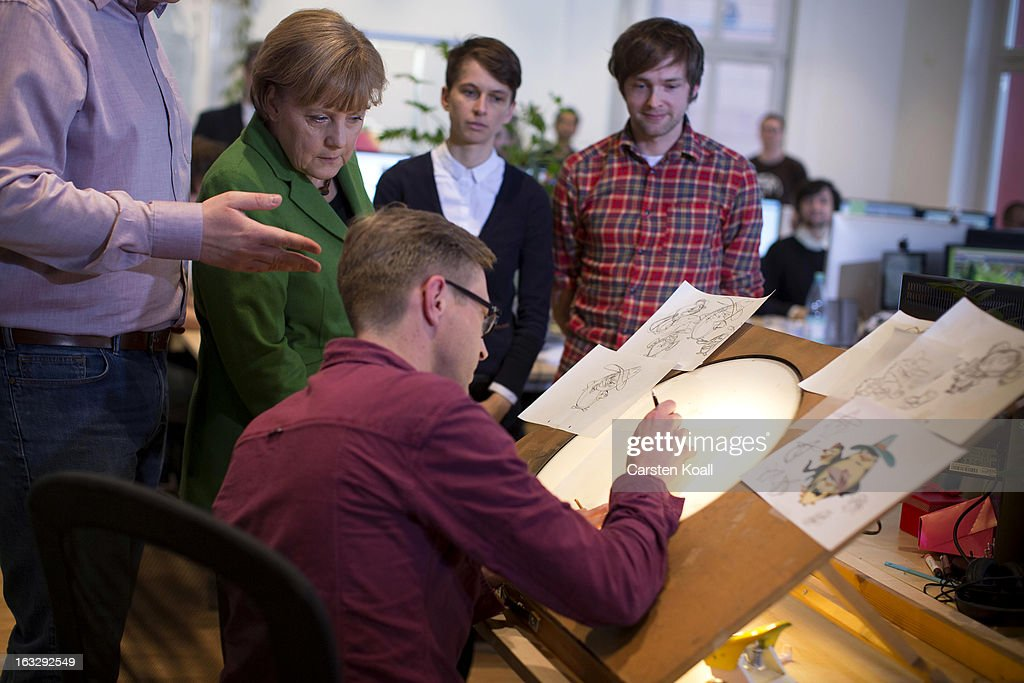 German Chancellor Angela Merkel (L), watches employee Gerben Steeks (2nd L), during a visit of the Wooga company, which makes social games for smartphones and tablets, on March 7, 2013 in Berlin, Germany. Berlin has drawn a significant number of startup companies in recent years, many of which are drawn by the city's hip reputation and its comparatively low cost of living.