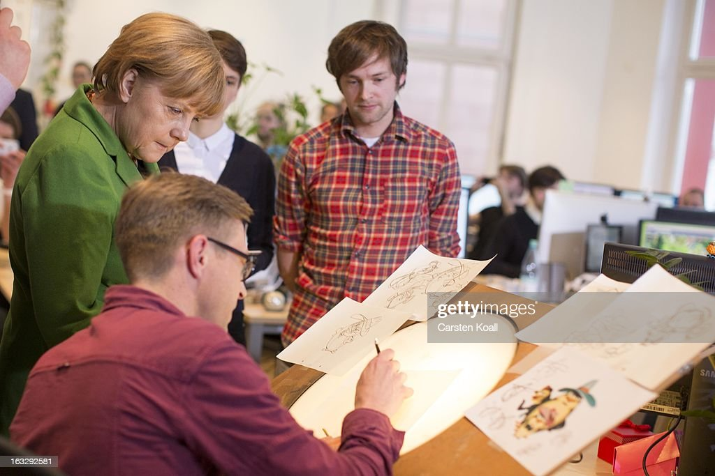 German Chancellor Angela Merkel (L), watches graphic artist Gerben Steeks (2nd L), during a visit at the Wooga company, which makes social games for smartphones and tablets, on March 7, 2013 in Berlin, Germany. Berlin has drawn a significant number of startup companies in recent years, many of which are drawn by the city's hip reputation and its comparatively low cost of living.