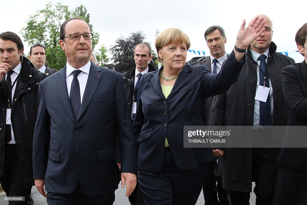 German Chancellor Angela Merkel (R) waves at the audience as she arrives with France's President Francois Hollande (L) for a remembrance ceremony to mark the centenary of the battle of Verdun, in Verdun, on May 29, 2016. The battle of Verdun, in 1916, was one of the bloodiest episodes of World War I. The offensive which lasted 300 days claimed more than 300,000 lives. / AFP / POOL / Thibault Camus