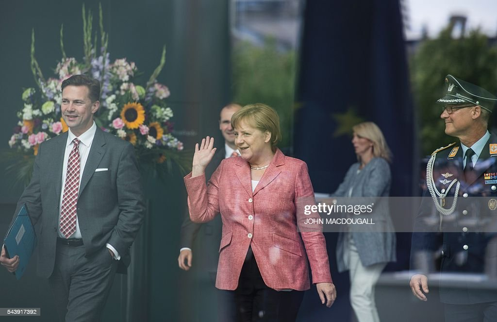 German Chancellor Angela Merkel (C) waves beside government's spokespers Steffen Seibert (L) as she heads out to welcome the members of the Presidency of Bosnia and Herzegovina at the chancellery in Berlin on June 30, 2016. At L is / AFP / John MACDOUGALL