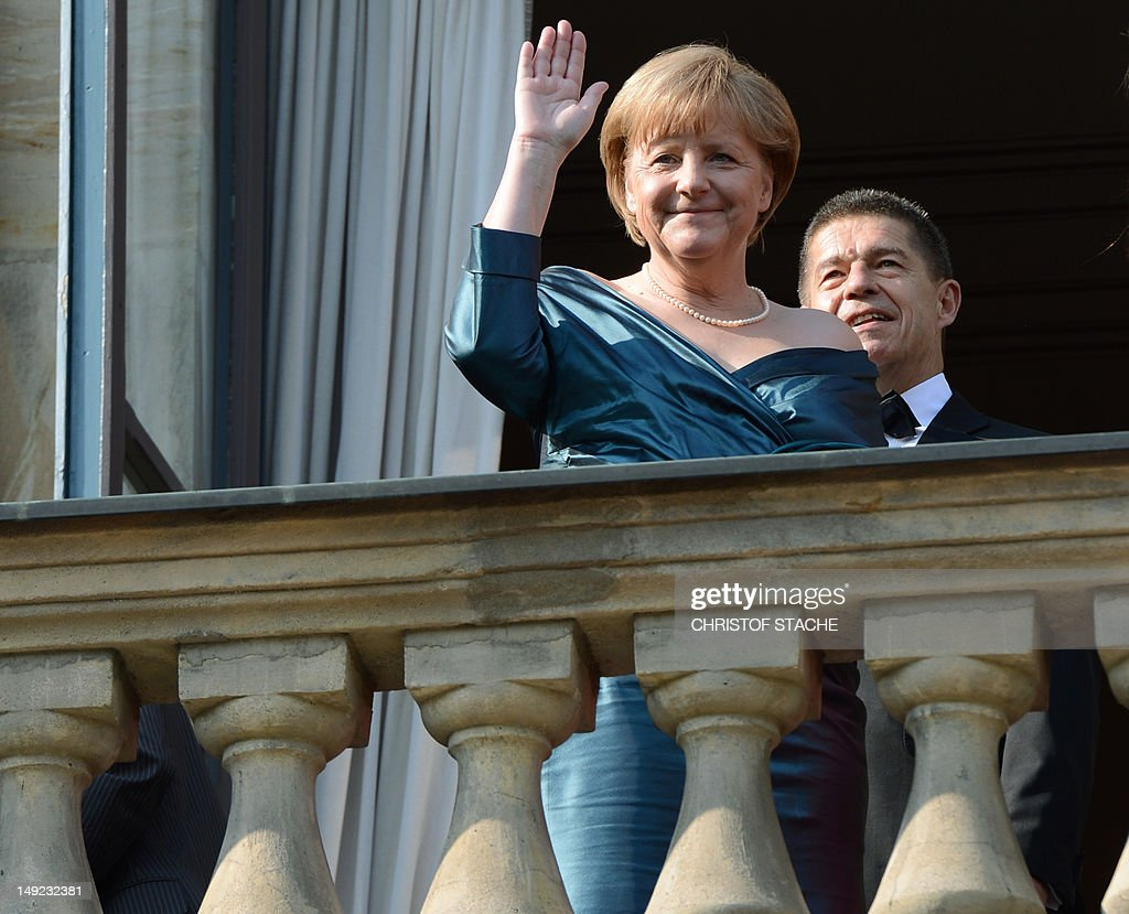 German Chancellor Angela Merkel waves from the balcony as she and her husband Joachim Sauer arrive for the opening of the Bayreuth Wagner Opera...