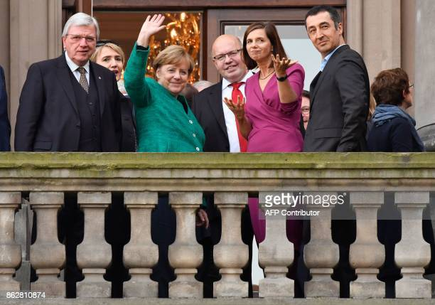 German Chancellor Angela Merkel waves from the balcony next top German Chief of Staff Peter Altmaier Parliamentary group coleaders of the Green Party...