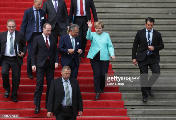 German Chancellor Angela Merkel waves to onlookers as she departs after sepaking at the annual congress of the Federation of German Industry on June...