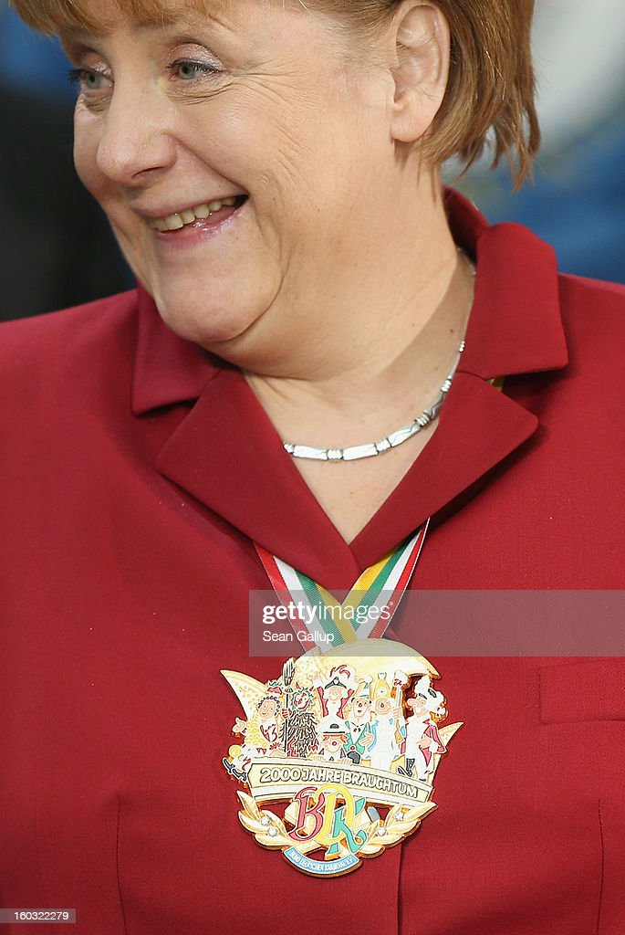 German Chancellor <a gi-track='captionPersonalityLinkClicked' href=/galleries/search?phrase=Angela+Merkel&family=editorial&specificpeople=202161 ng-click='$event.stopPropagation()'>Angela Merkel</a> wears a Carnival medal that reads: '2000 Years of Tradition' while meeting with Carnival delegates from all over Germany in an annual ceremony at the Chancellery on January 29, 2013 in Berlin, Germany. Germany is in the midst of Carnival season, which ends with its highpoint between Rose Monday and Ash Wednesday in a tradition common in several countries in Europe and the Americas.