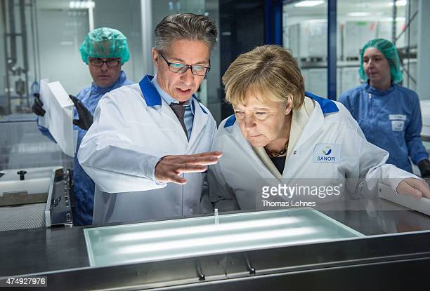 German Chancellor Angela Merkel wears a lab coat as she visits the new production facility for sterile glass vials at the Sanofi pharmaceuticals...