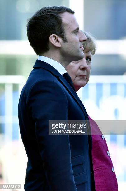 German Chancellor Angela Merkel welcomes French President Emmanuel Macron listen to the national anthems a day after the new French president took...