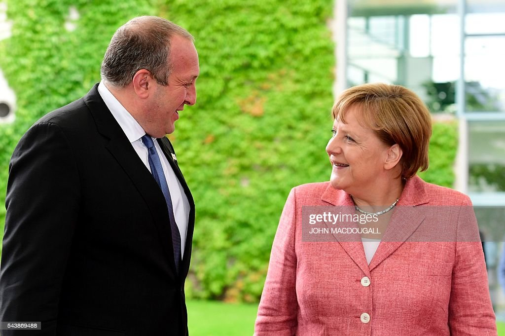 German Chancellor Angela Merkel welcomes Georgian President Giorgi Margvelashvili as he arrives for talks at the Chancellery in Berlin, on June 30, 2016. / AFP / John MACDOUGALL