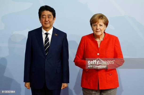 German Chancellor Angela Merkel welcomes Japanese Prime Minister Shinzo Abe as he arrives to attend the G20 summit in Hamburg northern Germany on...