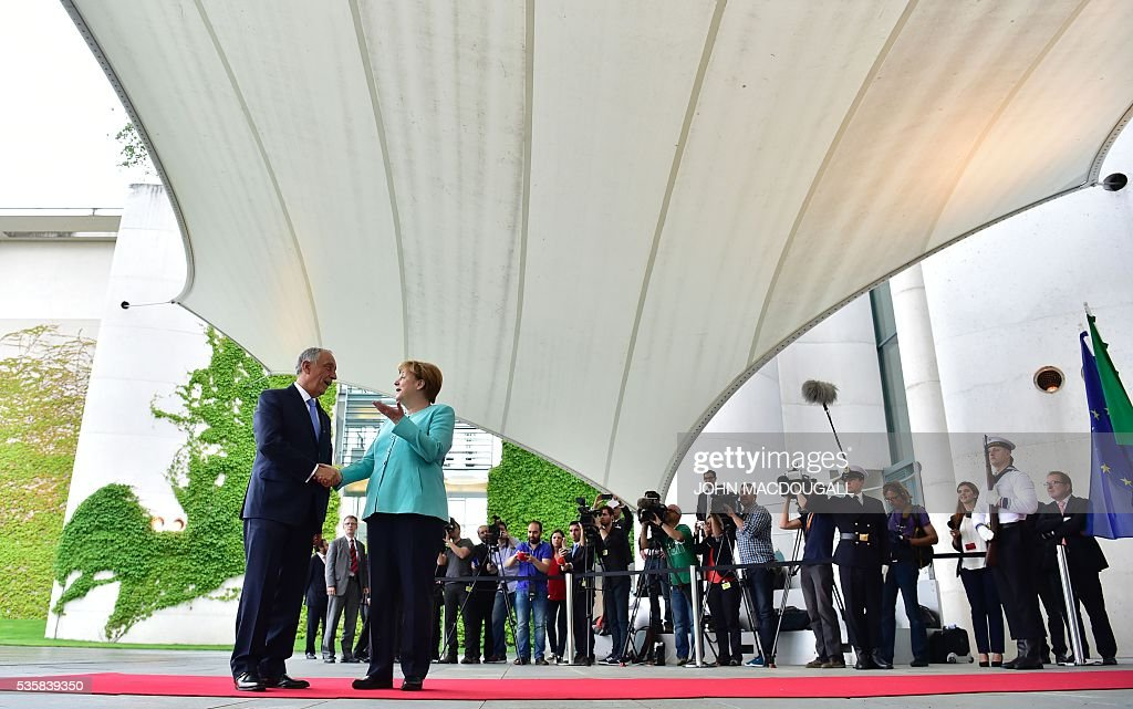 German Chancellor Angela Merkel (R) welcomes Portuguese President Marcelo Rebelo de Sousa in front of the Chancellery in Berlin on May 30, 2016. / AFP / John MACDOUGALL
