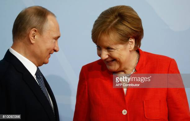 German Chancellor Angela Merkel welcomes Russia's President Vladimir Putin as he arrives to attend the G20 summit in Hamburg northern Germany on July...