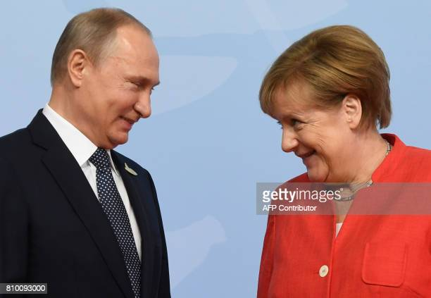 TOPSHOT German Chancellor Angela Merkel welcomes Russia's President Vladimir Putin as he arrives to attend the G20 summit in Hamburg northern Germany...