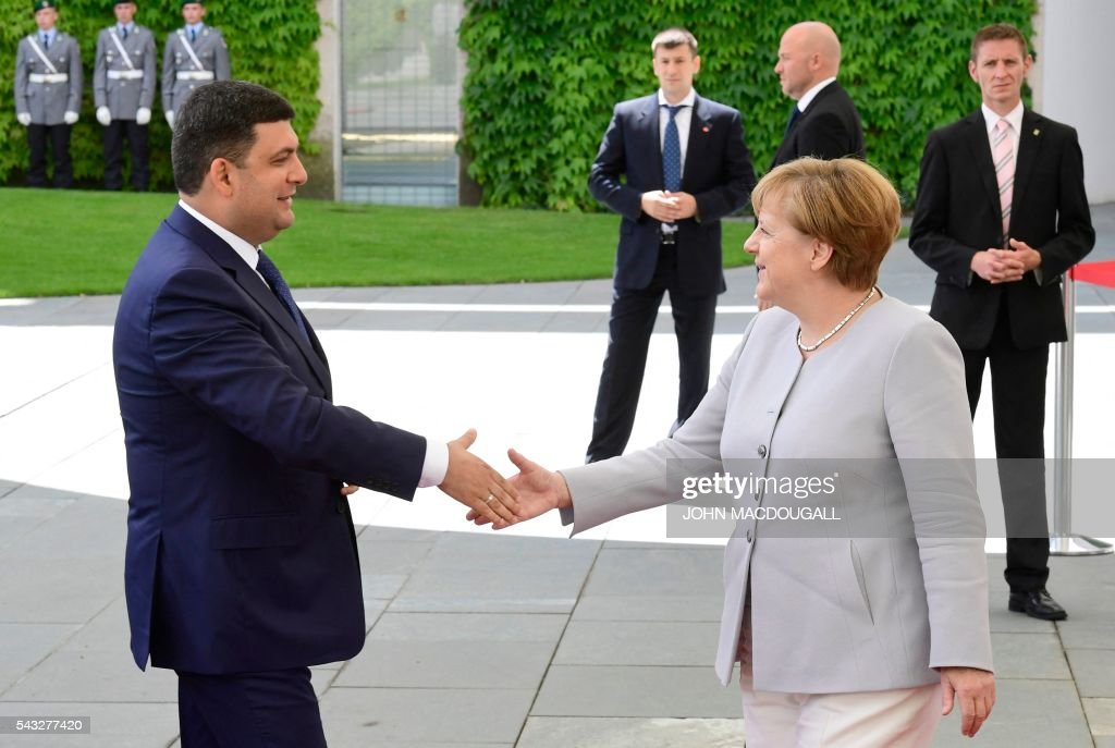 German chancellor Angela Merkel (R) welcomes Ukrainian Prime Minister Volodymyr Groysman upon arrival at the chancellery in Berlin on June 27, 2016. / AFP / John MACDOUGALL