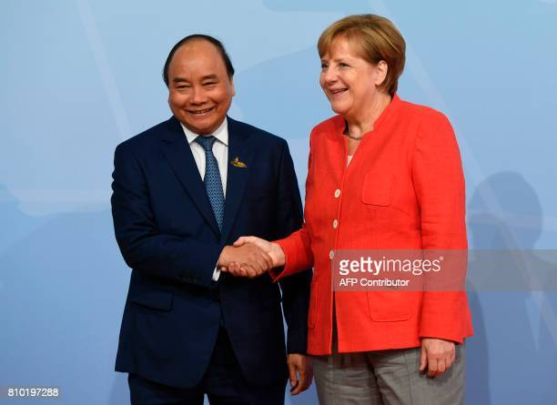 German Chancellor Angela Merkel welcomes Vietnam's Prime Minister Nguyen Xuan Phuc as he arrives to attend the G20 summit in Hamburg northern Germany...