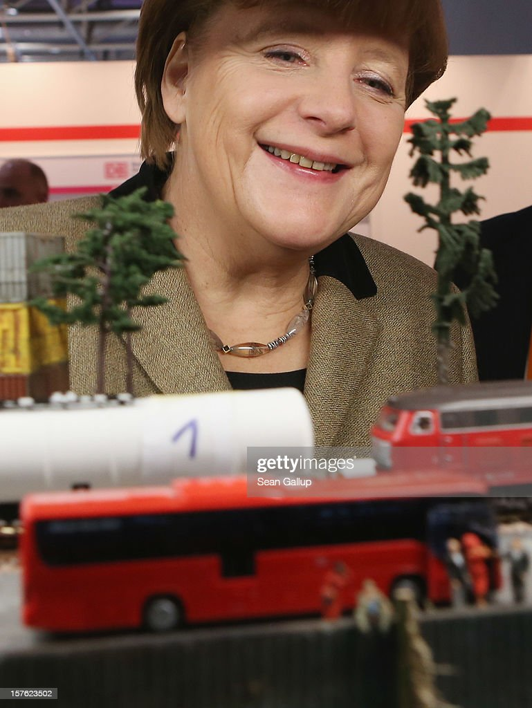 German Chancellor Angela Merkel, who is also chairwoman of the German Christian Democratic Union (CDU), looks at a model train at the stand of Deutsche Bahn while touring the exhibitors' hall at the CDU federal party convention on December 5, 2012 in Hanover, Germany. The CDU has a strong lead over its opponents though has recently lost the mayoral posts in several major German cities to opposition parties. Germany faces federal elections in 2013.