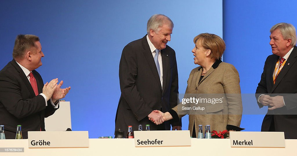 German Chancellor <a gi-track='captionPersonalityLinkClicked' href=/galleries/search?phrase=Angela+Merkel&family=editorial&specificpeople=202161 ng-click='$event.stopPropagation()'>Angela Merkel</a>, who is also chairwoman of the German Christian Democratic Union (CDU), congratulates <a gi-track='captionPersonalityLinkClicked' href=/galleries/search?phrase=Horst+Seehofer&family=editorial&specificpeople=4273631 ng-click='$event.stopPropagation()'>Horst Seehofer</a>, Chairman of the Christian Social Union (CSU), the Bavarian sister party of the CDU, after he spoke at the CDU federal party convention as CDU General Secretary <a gi-track='captionPersonalityLinkClicked' href=/galleries/search?phrase=Hermann+Groehe&family=editorial&specificpeople=6400355 ng-click='$event.stopPropagation()'>Hermann Groehe</a> (L) and Hesse Governor <a gi-track='captionPersonalityLinkClicked' href=/galleries/search?phrase=Volker+Bouffier&family=editorial&specificpeople=2371294 ng-click='$event.stopPropagation()'>Volker Bouffier</a> look on on December 5, 2012 in Hanover, Germany. The CDU has a strong lead over its opponents though has recently lost the mayoral posts in several major German cities to opposition parties. Germany faces federal elections in 2013.